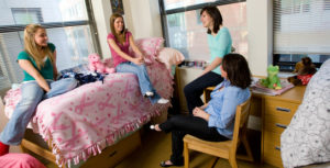 Four students having fun in their room at the dormitory, all of them are girls. They sit on the bed and taslk about something. One person sits on a chair.