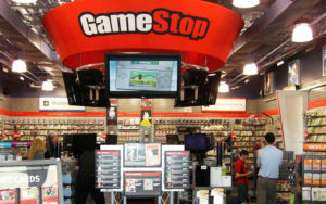 one of many gamestop stores, we can see their logo, and lot of customers shopping for the newest games.