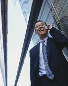 A young Japanese businessman is answering a phone call from a job candidate who follows up his interview with a call. The man is in a good mood and stands next to a business building.