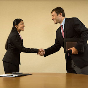 Candidate and interviewer shake hands, they are in a small office, we can see a brown wooden table and a job application on the table.