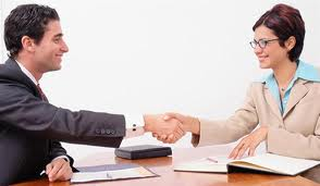 Woman with glasses and brown jacket shakes hand of a job applicant, a man in black jacket. We can see his job application on the table.