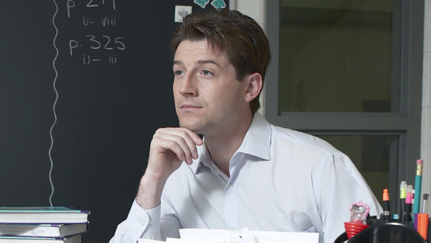A young teacher sits at his desk, looking at the students. We can see a pile of books and some pencils on the desk. There is a blackboard in the backgound of the picture.