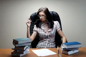 a secretary sits in a leather chair, looking at us. She has eight books on her working table, some papers, and a glass of water.