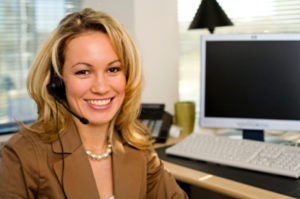 Receptuionist at work. A nice blonde lady in a jacket smiles at us, as she sits at her desk, wearing a headphone to answer phone calls.