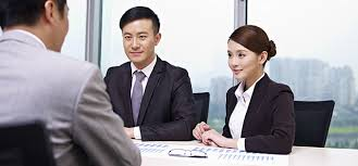 Illustration of an interview in a Japaneese company. The interviewers, man and woman, talk to a job candidate in a grey suit, another Japanese man, in a modern office.