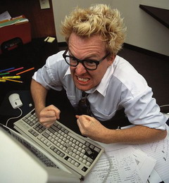 A programmer is angry, gesticulating in front of his computer. We can see a grey keyboard on the picture