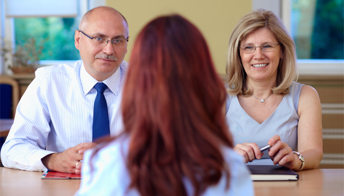 Duo of hiring managers talks to a job applicant. The second interview takes places in a school environment.
