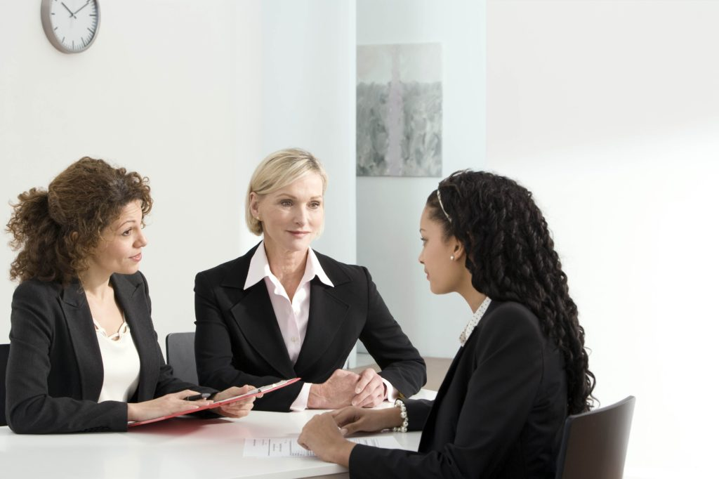 Two female interviewers lead an interview with a female job applicant, all of them wear black clothes, and we can see papers on the table.