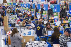 A picture of a long line of cash desks at Walmart. We can see plenty of cashier, and also many customers who pay for their shopping at the store.