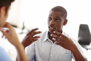 A man is explaining his motivation in a job interview, gesticulating with hands, keeping eye contact with the HR generalist.