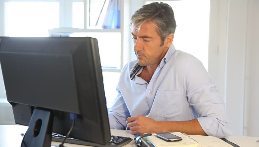 Older man sits in front of his computer, trying to prepare for an interview.
