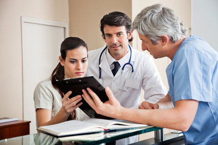 Three people in the medical practice. A physician, a medical receptionist, and a medicall assistant. They are looking at a medical record.