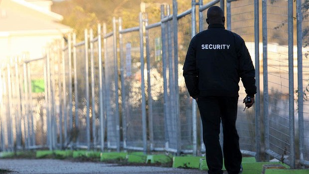 A security officer is walking around a wire fence, guarding the building. We can see a walkie-talkie in his hand, and he wears a black jacket with SECURITY written on his back.