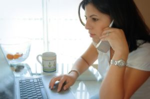 A woman is calling en employer, and at the same time reading an email from them. She is about to decline her interview. We can see a small aquarium and an empty porcelain cup on the table.