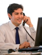 HR manager is interviewing people on the phone. He sits at his desk, in front of a computer screen, and holds a phone in his hand.