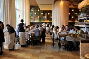 picture of a busy restaurant, we can see waiters, and many people dining at their tables