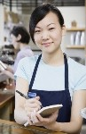 Barista in her job, a girl of Asian origin, she is taking an order from a customer. She wears white shirt and a blue apron.