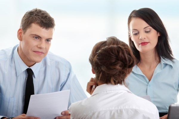 A woman in white shirt interviews for a job. The interviewers, man and woman, lead the interview. The man holds the resume of the job candidate in his hands.