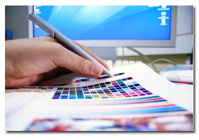 A graphic designer looks at the color palette, and marks some choices with a pencil. We can see their hand and a computer screen in the background