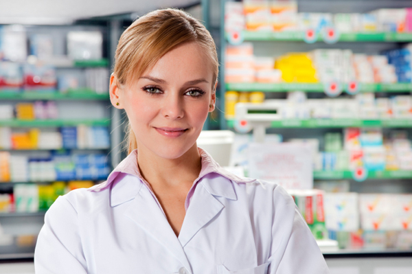 A young pharmacist, a blonde American, stands in front of a cash desk in a pharmacy. We can see a lot of medications in the back of the picture.