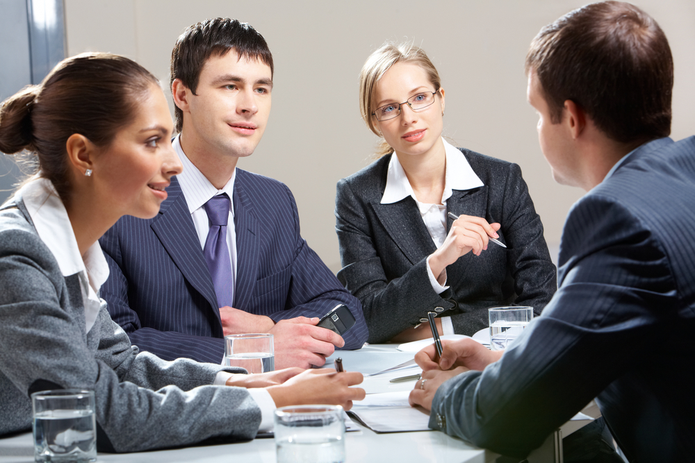 A lively discussion in a job interview. we can see four people dressed in business atire, talking to each other and gesticulating