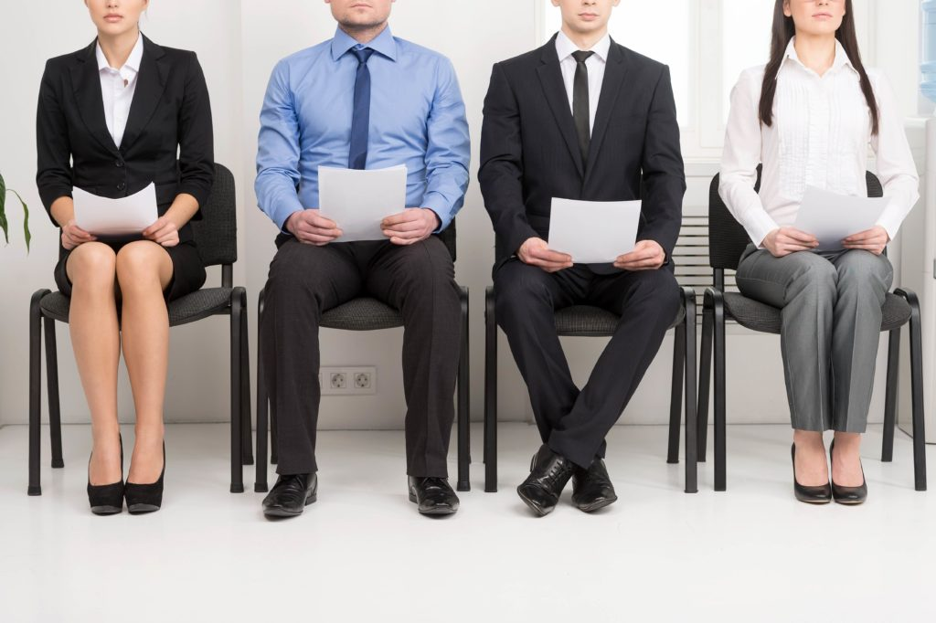 Four job candidates are nervously waiting for their training specialist interview, The hold resumes in hands, and sit on black chairs.