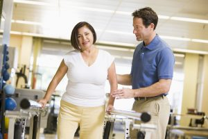 the therapist helps the woman to learn to walk again, after an injury. We can see her walking on a belt.