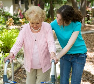 An occupational therapist exercises with a patient, and older lady, who is learning to walk again, after an injury. They are outside, in a hospital garden