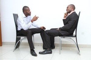 A role play - two men try to demonstrate their teamwork abilities in a role play. We can see them talking and gesticulating with their hands.