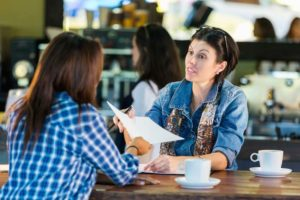 Two women are discussing career change ideas over a cup of coffee. They sir in a nice cafeteria, and we can see more guests in the background.
