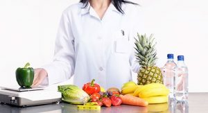 Dietitian standing next to a table full of healthy foods, fruits and vegetables.