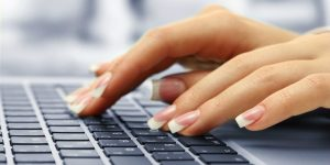 A woman types on a keyword, we can see her nice fingernails.