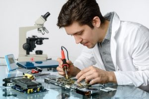 Electrical Engineer is working on a new design. He's wearing white shirt, and we can see a microscope on the table.