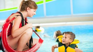 A girl is doing her lifeguard job, keeping her eye on one of the children in the pool