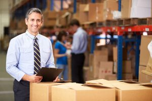 Logistics manager at work. The man stands next to a pile of boxes in the warehouse.