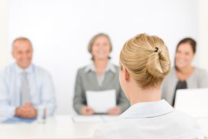 A young woman interviews in a front of a panel of three interviewers, for a position in healthcare.