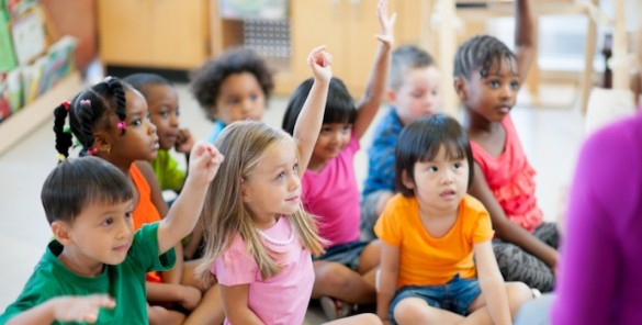 children at preschool, they hold their hands up, wanting to answer a question of the teacher.