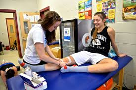 Athletic traner helps a female patient with taping her leg