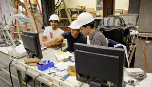 A group of engineers works together on a difficult task.
