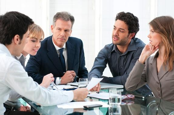 A group of managers discusses a change in a meeting.