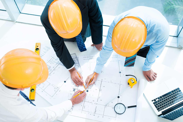 Three industrial engineers in yellow helmets work together on a new design.