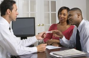 A mortgage loan officer talks to a young couple about an options for the mortgage.