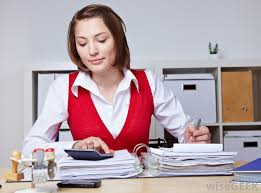 Female clerk in a nice red blouse works with the papers in the office.