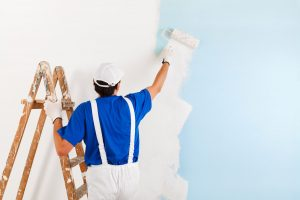 Man in blue overals paints the wall with white color.