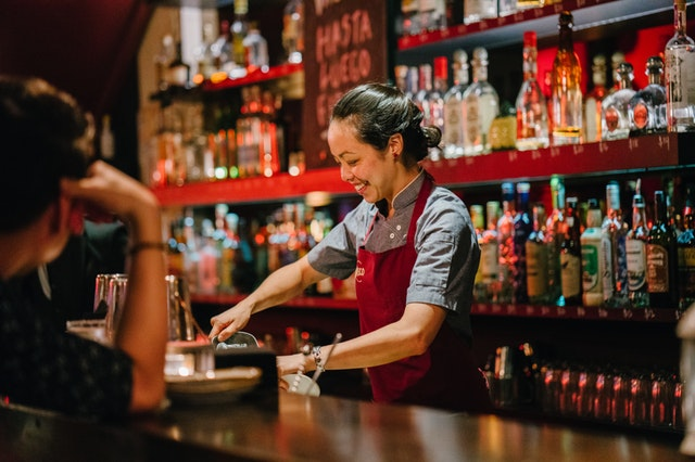 happy woman works behind a bar