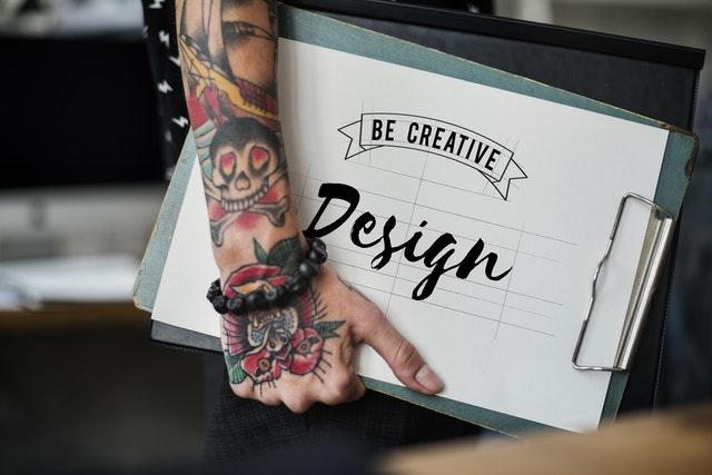 Man with a tatooed arm carries his design portfolio