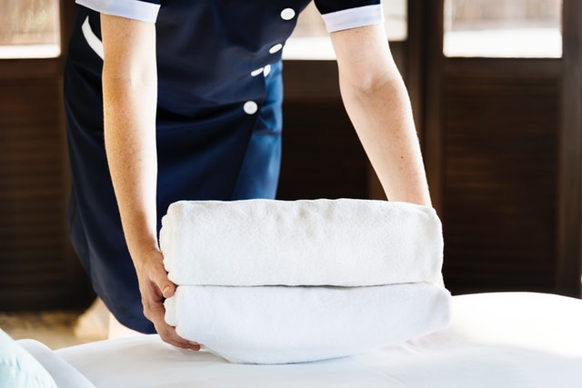 hotel employee handing some towels on the bed