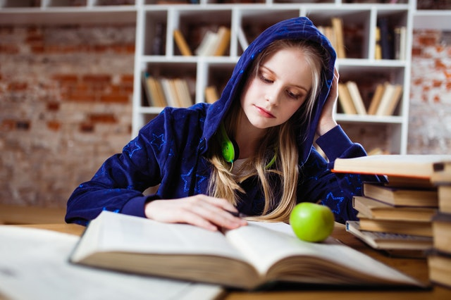 teen in a blue hoodie is studying