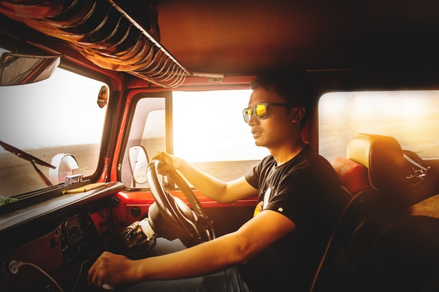 young man with sunglasses drives a truck