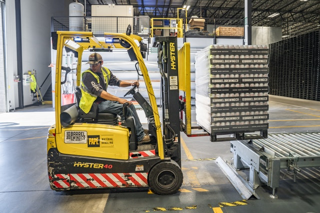 Forklift operator in work, with a nice yellow forklift